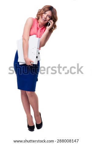 Full length portrait of a laughing businesswoman talking on the phone and holding folders isolated on a white background. Looking at camera - stock photo