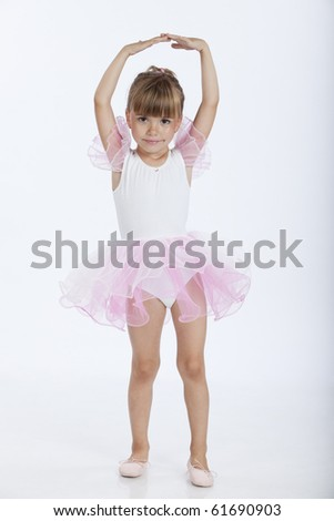 Full length portrait of a little pretty ballerina performing a new ballet position, studio image - stock photo