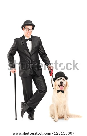 Full length portrait of a magician with bow tie holding cane and dog isolated on white background - stock photo