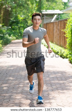 Full-length portrait of a male jogger running along the path - stock photo