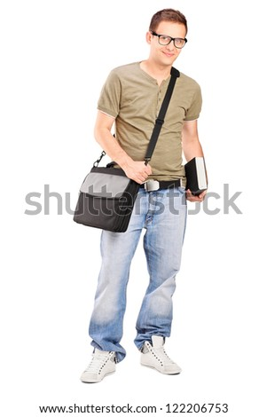 Full length portrait of a male student with shoulder bag holding a book isolated on white background - stock photo