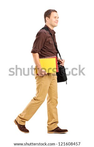 Full length portrait of a male student with shoulder bag holding books and walking isolated on white background - stock photo