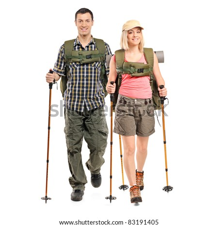 Full length portrait of a man and woman with backpacks and hiking poles isolated on white background - stock photo