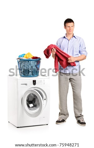 Full length portrait of a man holding a blouse and a washing machine isolated on white - stock photo