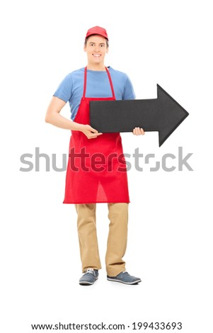 Full length portrait of a man in apron holding a big black arrow pointing right isolated on white background - stock photo