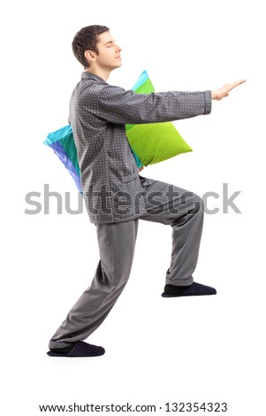 Full length portrait of a man in pajamas sleepwalking with a pillow in his hand isolated on white background - stock photo