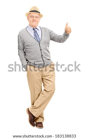 Full length portrait of a man leaning against a wall and giving a thumb up isolated on white background - stock photo