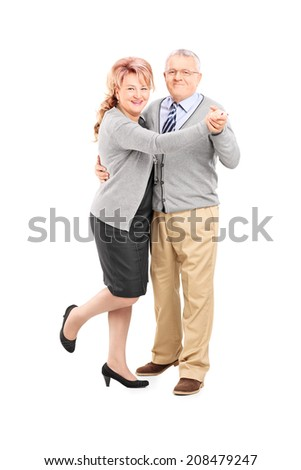 Full length portrait of a mature couple dancing tango isolated on white background - stock photo