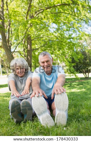 Full length portrait of a mature couple stretching hands to legs at the park - stock photo