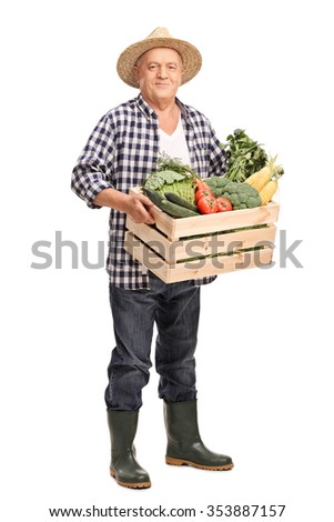 Full length portrait of a mature farmer carrying a wooden crate full of fresh vegetables and looking at the camera isolated on white background - stock photo