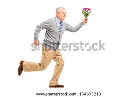 Full length portrait of a mature gentleman running with flowers, isolated on white background - stock photo
