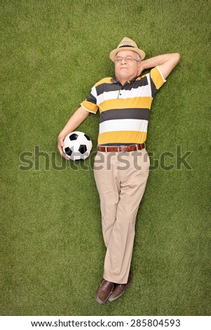Full length portrait of a mature man lying on grass and holding a soccer ball beside him  - stock photo