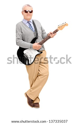 Full length portrait of a mature man with electric guitar leaning against wall, isolated on white background - stock photo