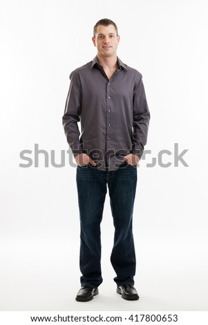 Full length portrait of a mid 30s casual business man with hands in pockets isolated on a white background - stock photo