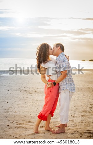 Full length portrait of a middle aged couple kissing on the beach at sundown in Jamaica - stock photo