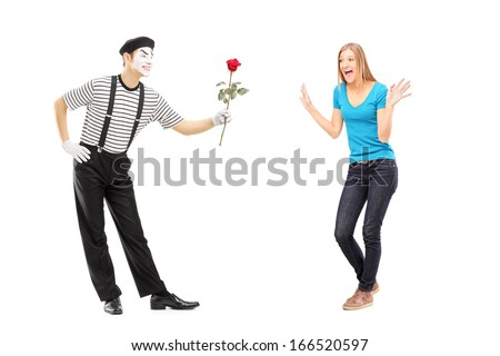 Full length portrait of a mime artist giving a rose flower to an excited woman isolated on white background - stock photo