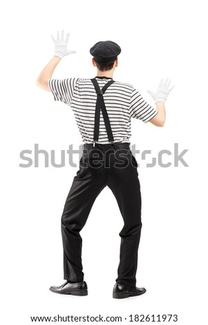 Full length portrait of a mime artist performing isolated on white background, rear view - stock photo