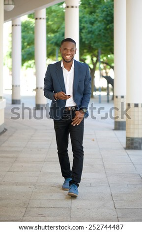 Full length portrait of a modern cool black guy walking with mobile phone - stock photo