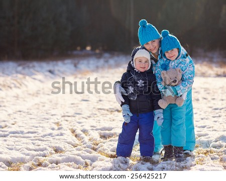 Full length portrait of a mother and her cute little son and daughter hugging a teddy bear outdoors on a winter's day - stock photo