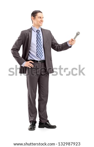 Full length portrait of a professional male reporter holding a microphone, isolated on white background - stock photo