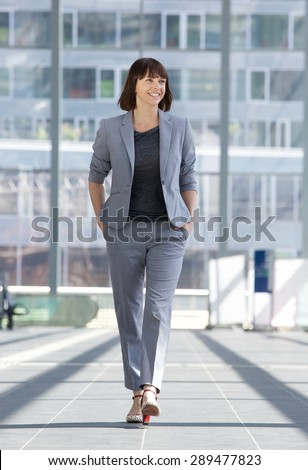 Full length portrait of a relaxed business woman smiling and walking  - stock photo