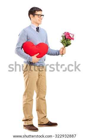 Full length portrait of a romantic man holding a red heart and a bouquet of flowers isolated on white background - stock photo