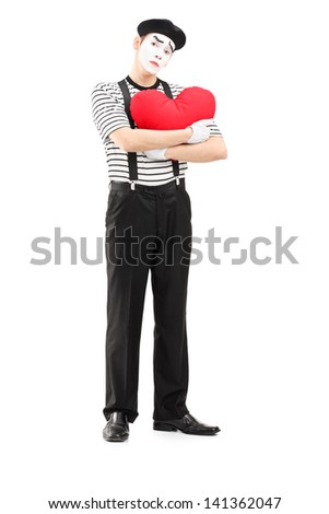 Full length portrait of a sad mime artist holding a red heart isolated on white background - stock photo