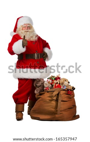 Full length portrait of a Santa Claus posing near a bag full of gifts and thumbs up isolated on white background - stock photo