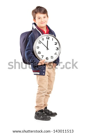 Full length portrait of a school boy with backpack holding a wall clock and looking at camera, isolated on white background - stock photo