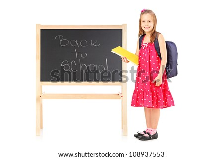 Full length portrait of a schoolgirl holding a notebook and posing next to a board isolated on white background - stock photo