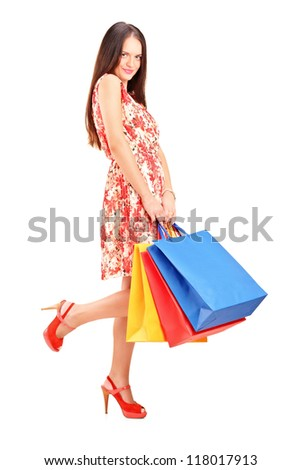 Full length portrait of a seductive female posing with shopping bags isolated on white background - stock photo