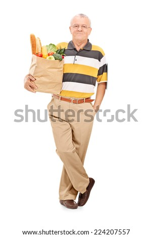 Full length portrait of a senior gentleman posing with bag full of groceries isolated on white background - stock photo