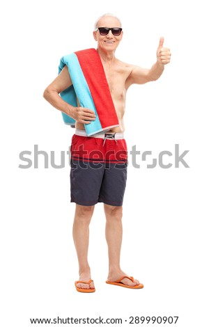 Full length portrait of a senior in blue swim trunks carrying a towel over his shoulder and giving a thumb up isolated on white background - stock photo