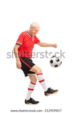 Full length portrait of a senior man in a red jersey juggling a football and smiling isolated on white background - stock photo