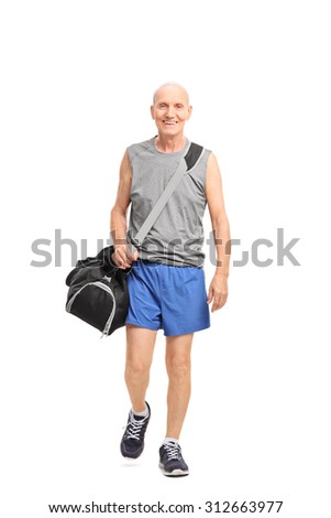 Full length portrait of a senior man in sportswear carrying a sports bag and walking isolated on white background - stock photo