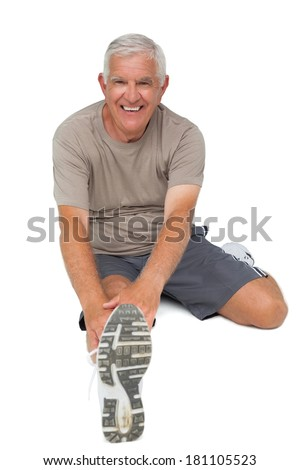 Full length portrait of a senior man stretching hands to leg over white background - stock photo