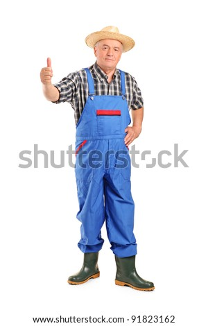 Full length portrait of a senior smiling farmer giving a thumb up isolated on white background - stock photo