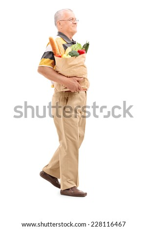 Full length portrait of a senior walking with a bag full of groceries isolated on white background - stock photo