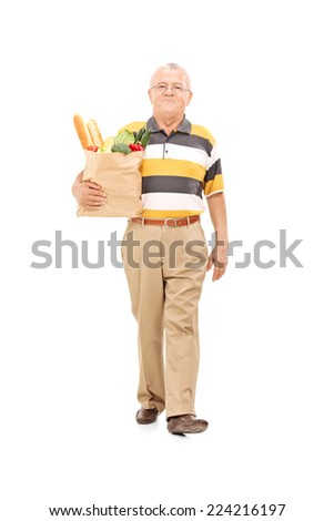 Full length portrait of a senior walking with a bag of groceries isolated on white background - stock photo