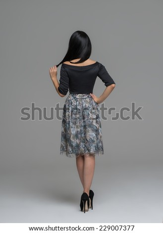 Full Length Portrait of a Sexy Brunette Woman in Fashion Dress back view - stock photo