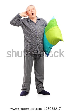 Full length portrait of a sleepy mature man in pajamas holding a pillow isolated on white background - stock photo