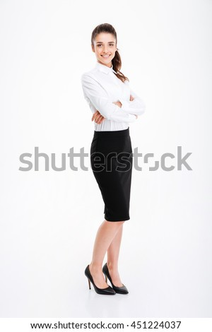 Full length portrait of a smiling businesswoman standing with arms folded isolated on a white background - stock photo