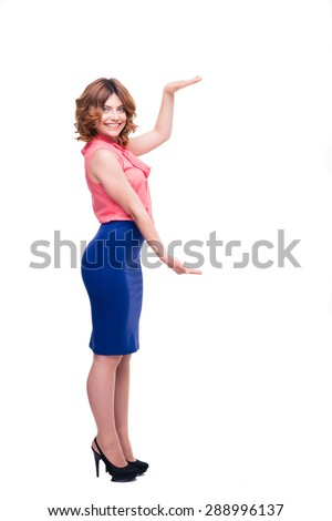 Full length portrait of a smiling charming woman holding copyspace on palms isolated on a white background. Looking at camera - stock photo