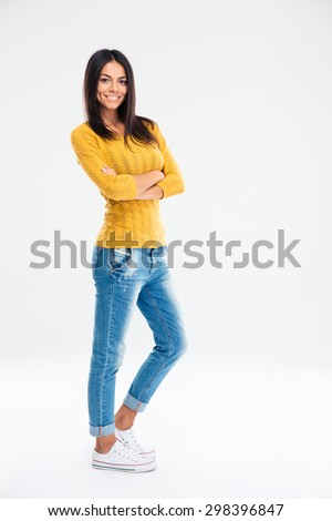 Full length portrait of a smiling cute woman standing with arms folded isolated on a white background - stock photo