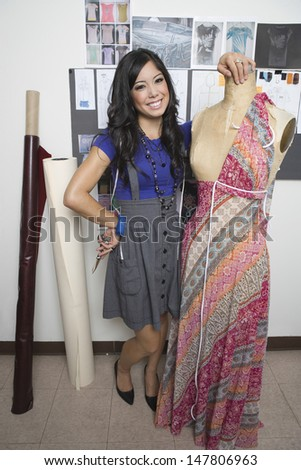 Full length portrait of a smiling female fashion designer with dummy - stock photo