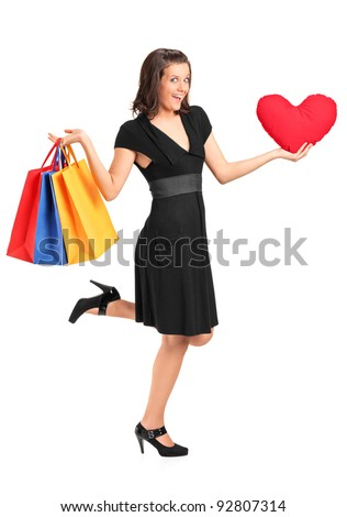 Full length portrait of a smiling female holding a red heart shaped pillow and shopping bags isolated on white - stock photo