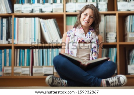 Full length portrait of a smiling female student against bookshelf reading a book on the library floor - stock photo