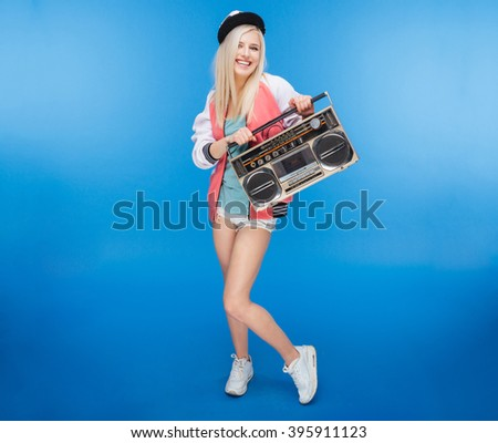 Full length portrait of a smiling female teenager holding retro boom box on blue background - stock photo