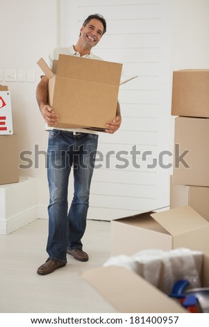 Full length portrait of a smiling man carrying boxes in new house - stock photo