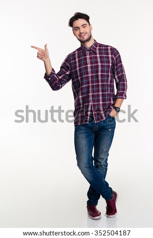 Full length portrait of a smiling man pointing finger away isolated on a white background - stock photo